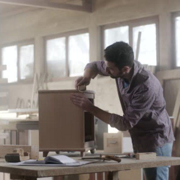 Man carpenter using sandpaper for finishing work on piece of furniture